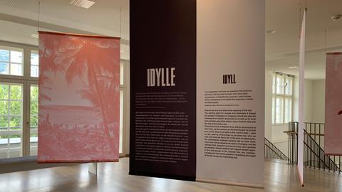 Längliche rote, weiße und schwarze Plakate mit Text hängen in einem Foyer im Deutschen Filminstitut und Filmmuseum.