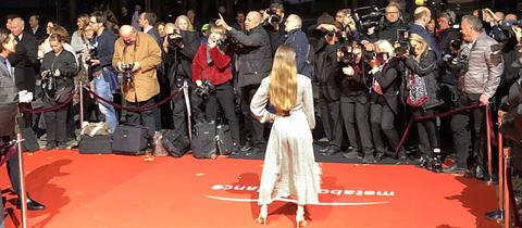 Frau posiert auf dem roten Teppich für die Fotografen