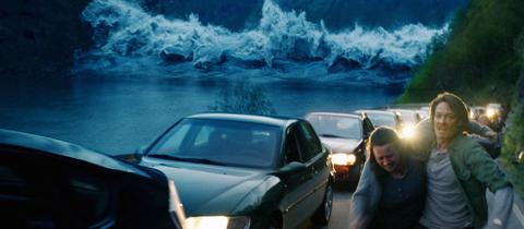 """Szene aus dem norwegischen Film """"Bolgen"""": Menschen und Autos flüchten vor einer riesigen Welle."""