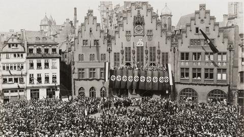 """Ausstellung """"Frankfurt und der NS"""", Schwarzweiß-Bild des Römerbergs, auf dem sich eine Menschenmasse versammelt hat, am Rathaus hängen Hakenkreuzfahnen"""