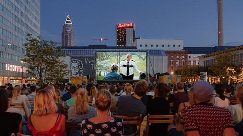 Freiluftkino Frankfurt - Menschen sitzen vor einer Großleinwand auf der ein Film läuft.