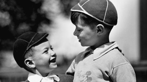 Freunde - zwei Jungs, die einander anlächeln.