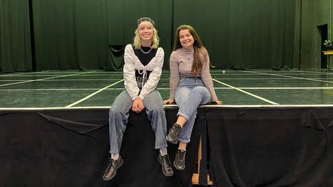 Zwei junge Mädchen sitzen am Rand einer Bühne, die Beine baumeln von der Kante