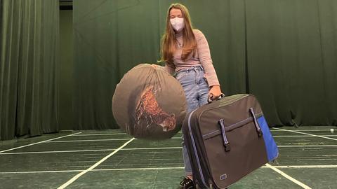 Ein Mädchen steht auf einer Bühne. Sie trägt einen Koffer und einen Seesack.