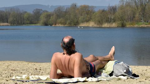 Ein Mann in Badehose liegt auf einem Handtuch im Sand an der Fuldaaue in Kassel.
