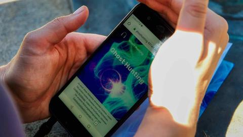 """Hand hält Smartphone mit """"Ghosthunting"""" auf dem Bildschirm"""
