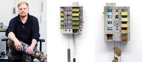Der Künstler Guido Zimmermann mit zwei seiner Kuckucksuhren, die wie Frankfurter Hochhäuser gestaltet sind