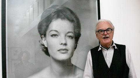 Der Fotograf Franz Christian Gundlach steht vor seinem Fotowerk von Romy Schneider.