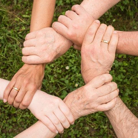 Miteiander verbundene Hände, die einen Kreis bilden