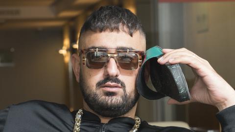 Rapper Haftbefehl posiert und hält sich eine Sandale ans Ohr.