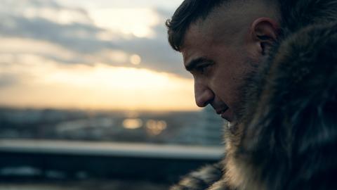 Rapper Haftbefehl - Aufnahme im Profil - im Hintergrund: Sonnenuntergang