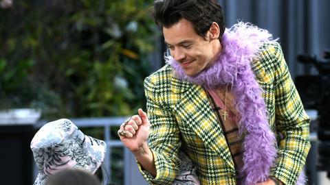Harry Styles: Mann mit Karojackett und rosa Federboa grüßt eine Frau im Publikum.
