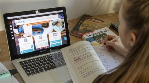 Eine Schülerin sitzt an am Schreibtisch und bearbeitet Aufgaben an einem Tablet