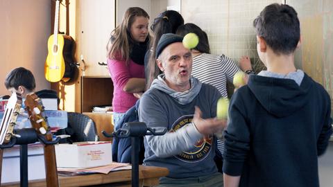 Herr Bachmann im Klassenzimmer, mit Tennisbällen jonglierend und umgeben von Schülerinnen und Schülern.