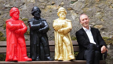 Ottmar Hörl sitz mit drei Gutenbergs auf einer Parkbank