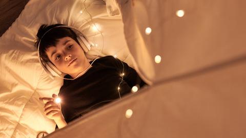 Ein Junge mit Kopfhörern liegt im Bett und leuchtet mit einer Taschenlampe.