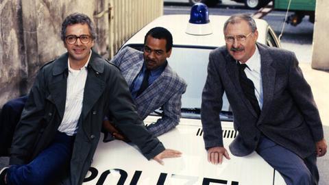 Mit Schnurrbart und kariertem Sakko lehnt Charles M. Huber 1985 als Kommissar Henry Johnson lässig auf der Motorhaube eines Polizeiauto.