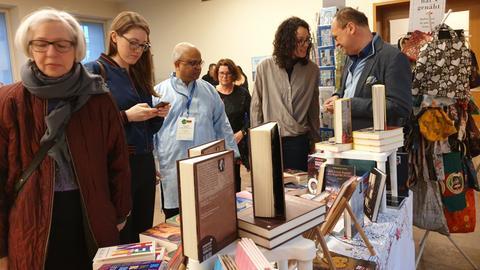 Menschen stehen an einem Büchertisch