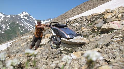 Mann schiebt Kinderwagen auf Alpenpfad