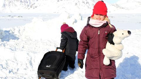 Kinder mit Rollkoffer und Plüscheisbär in Grönland