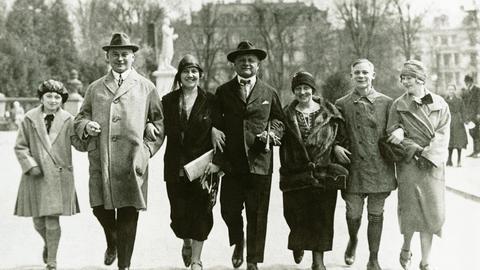 Sieben Menschen in Kleidung der 1920er Jahre Arm in Arm