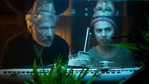 """Filmstill """"Eine Handvoll Wasser"""": Jürgen Prochnow und Milena Pribak alias Konrad und Thurba betrachten ein Aquarium."""