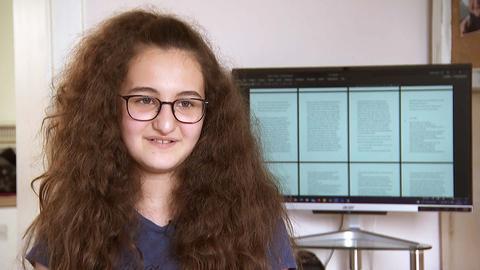 Liliana Huber vor ihrem Computer, auf dessen Screen beschriebe Seiten sichtbar sind.