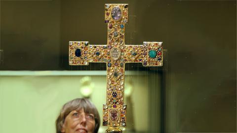 Kaiser-Heinrich-Kreuz hinter einer Glasscheibe in der Ausstellung. Daneben ein Kopf einer Frau, die es betrachtet.