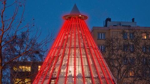 Rot angestrahlt leuchtet eine Pyramide, die ein offenes Buch darstellen soll.