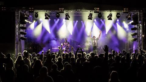 Zuschauer vor der Bühne - Bühne in lilafarbenes Licht getaucht