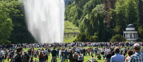 Menschen schauen sich eine Wasserfontäne an