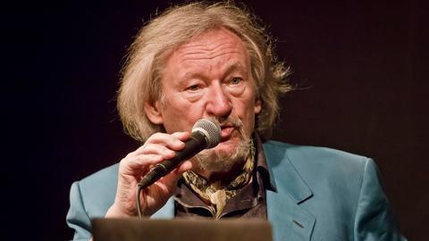 Klaus Theweleit mit einem Mikrofon in der Hand