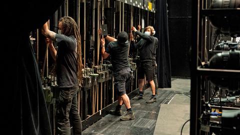 Bühnentechniker ziehen an dicken großen Seilen, um die Kulissen zu bewegen.