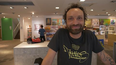 Engin Dogan: Mann mit Bart und schwarzem T-Shirt, der in einem Raum voll von Kunstwerken steht