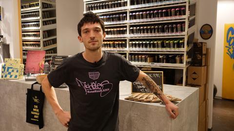 Luis Kannengießer: Mann in schwarzem T-Shirt vor einem Regal