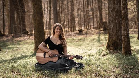 Lara Eckert sitzt mit Gitarre im Wald