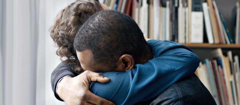 Ein schwarzer Mann und eine weiße Frau umarmen sich.