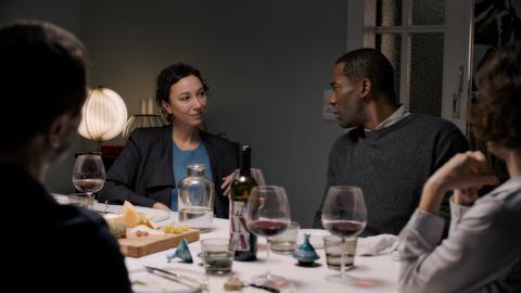 Eine weiße Frau und ein schwarzer Mann sitzen am Tisch beim Essen mit anderen Menschen