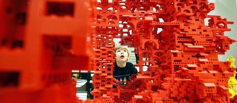 Ein Junge bestaunt ein Kunstwerk auf der Lego-Baustelle im Architekturmuseum Frankfurt.