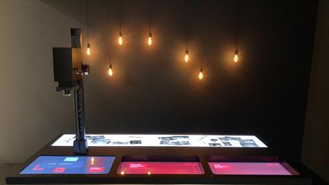 Ein dunkler Raum mit Glühbirnen und einem Tisch mit Displays