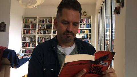 Mann liest aus Buch