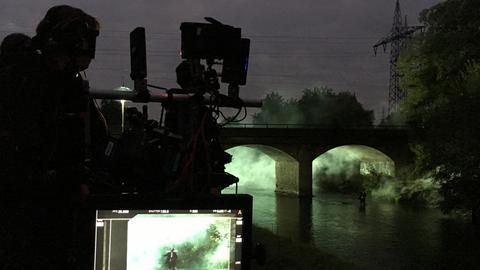 Eine dunkle Brücke über die Nidda wird bei Nacht gefilmt