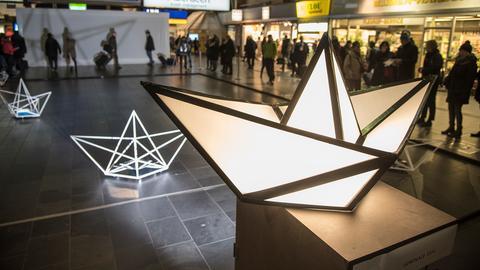 Leuchtende Papierschiffe in der Vorhalle des Frankfurter Hauptbahnhofs