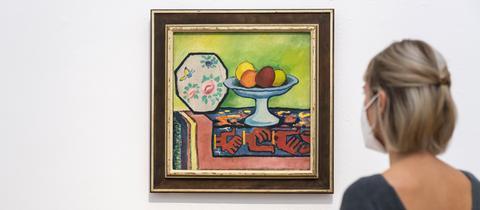 Eine Frau betrachtet ein Stillleben mit Apfelschale von August Macke