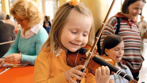 Ein kleines Mädchen probiert eine Geige aus