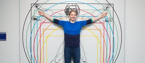 Leonardo im Mathematikum - eine Frau steht vor der Abbildung des vitruvianischen Menschen - den idealisierten Proportionen