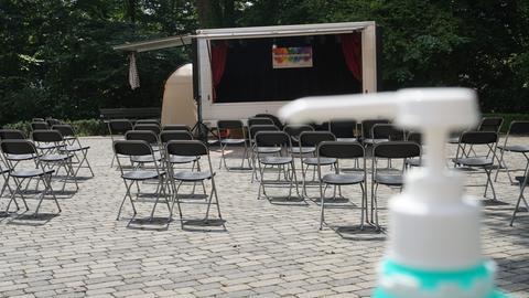 Ein aufgeklappter ehemaliger Imbisswagen als Bühne, davor Klappstühle