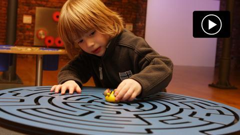 Spielendes Kind an einem Labyrinth im Mini-Mathematikum Gießen