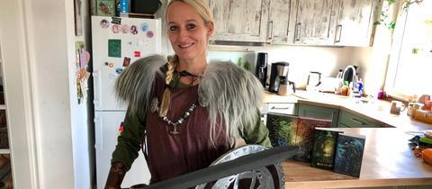 Frau in Wikingerkleidung in ihrer Kücher mit Büchern