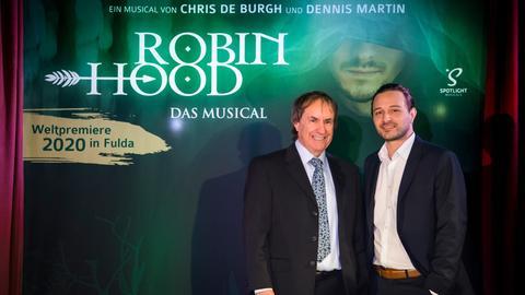 Chris de Burgh (li.) und Musical-Macher Dennis Martin vor einem Plakat des Musicals Robin Hood
